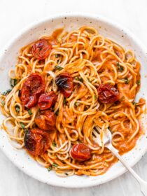 Roasted cherry tomato pasta sauce on spaghetti on a white plate.