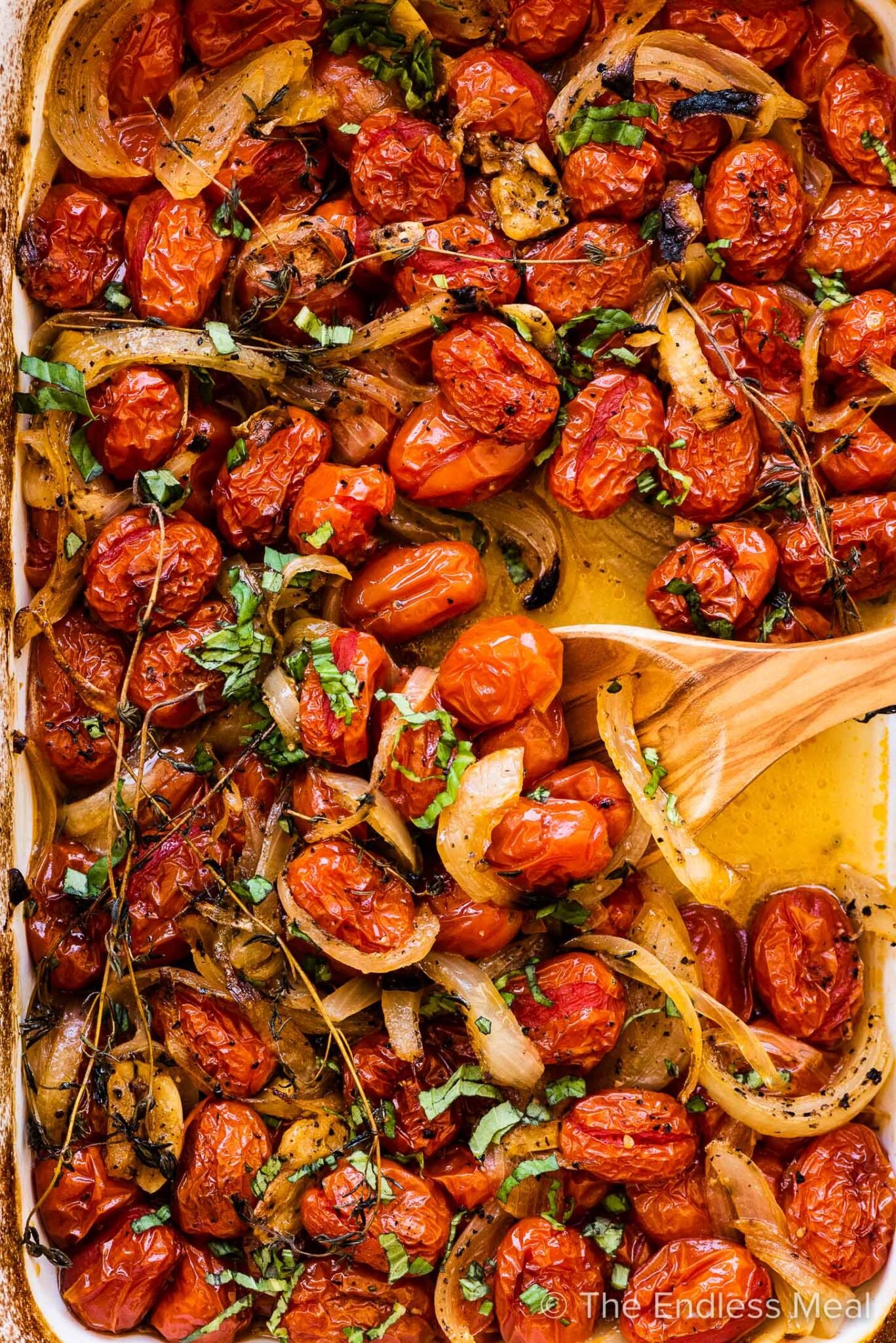 Roasted cherry tomatoes in a baking dish with a wooden spoon.