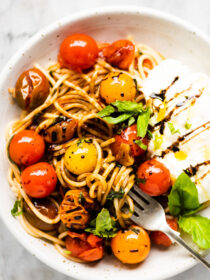 This summer pasta recipe with burrata on a white plate.