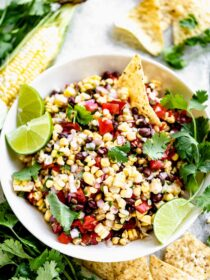 a bowl of corn salsa with a chip in it, garnished with cilantro sprigs and lime wedges