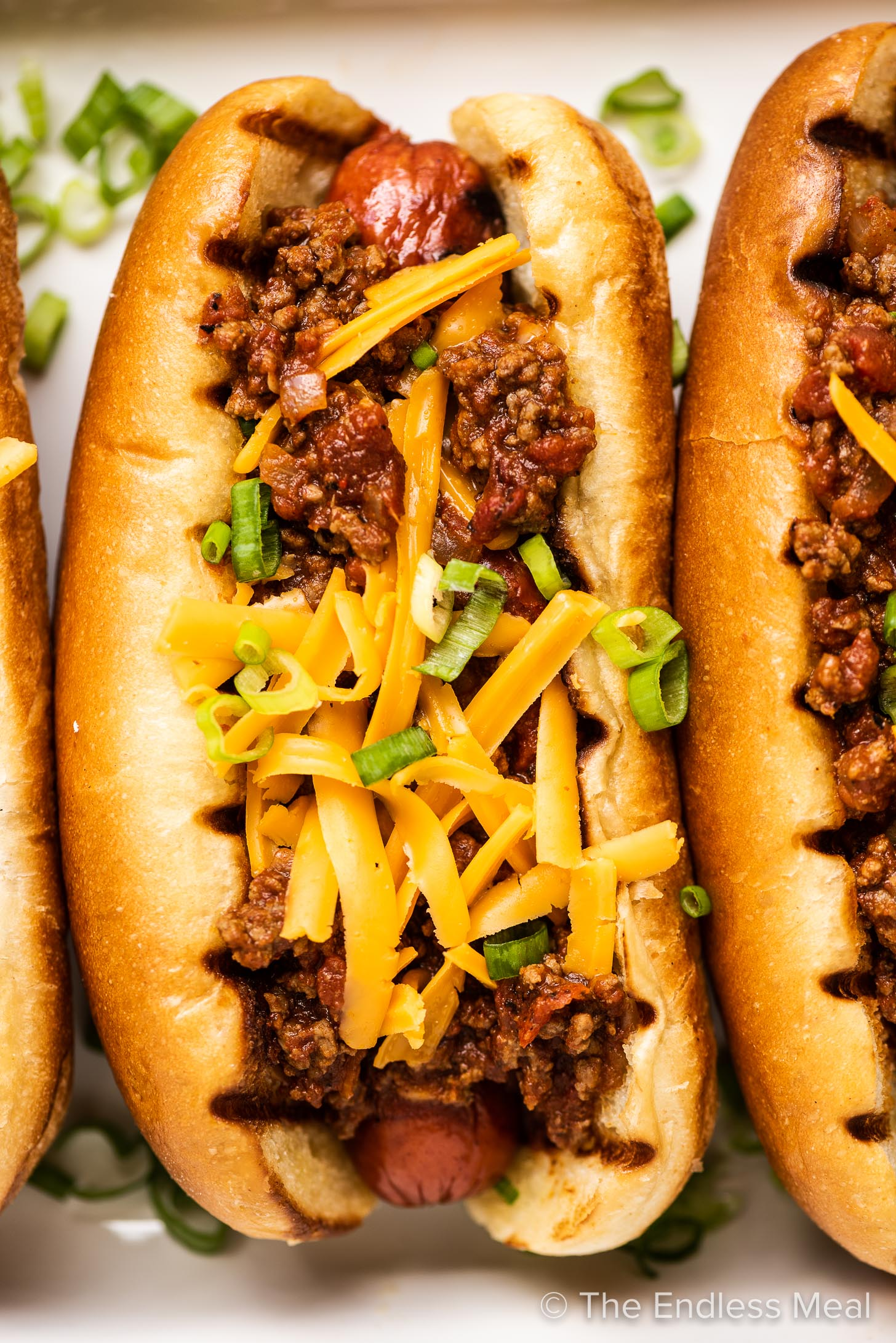 A close up of a chili cheese dog.