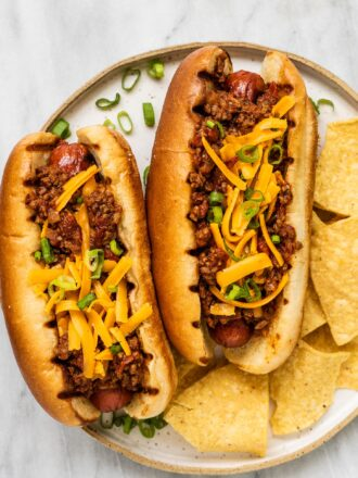 Two chili dogs on a plate with chips.
