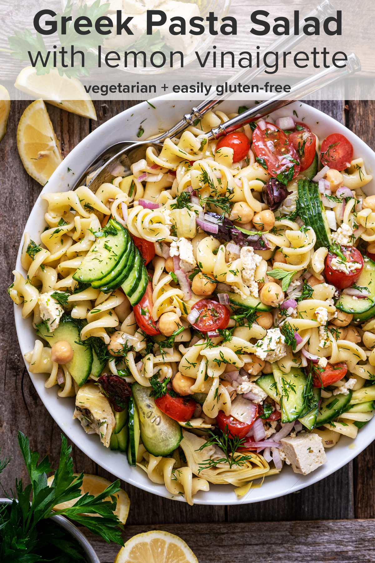 Greek pasta salad in a white serving bowl with the recipe title on top of the picture.