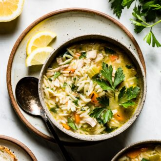 Lemon Chicken Orzo Soup in a bowl with a spoon on the side