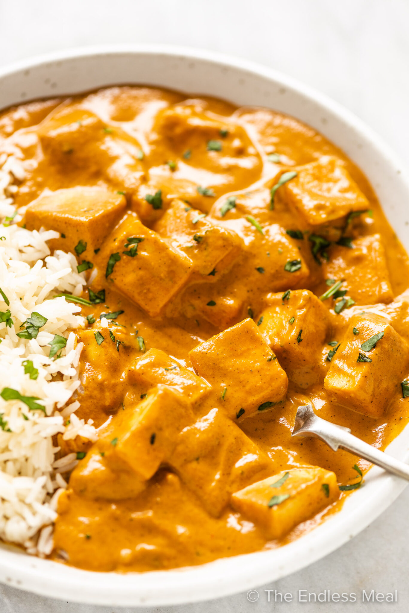 Paneer Butter Masala in a white bowl with a side of rice.