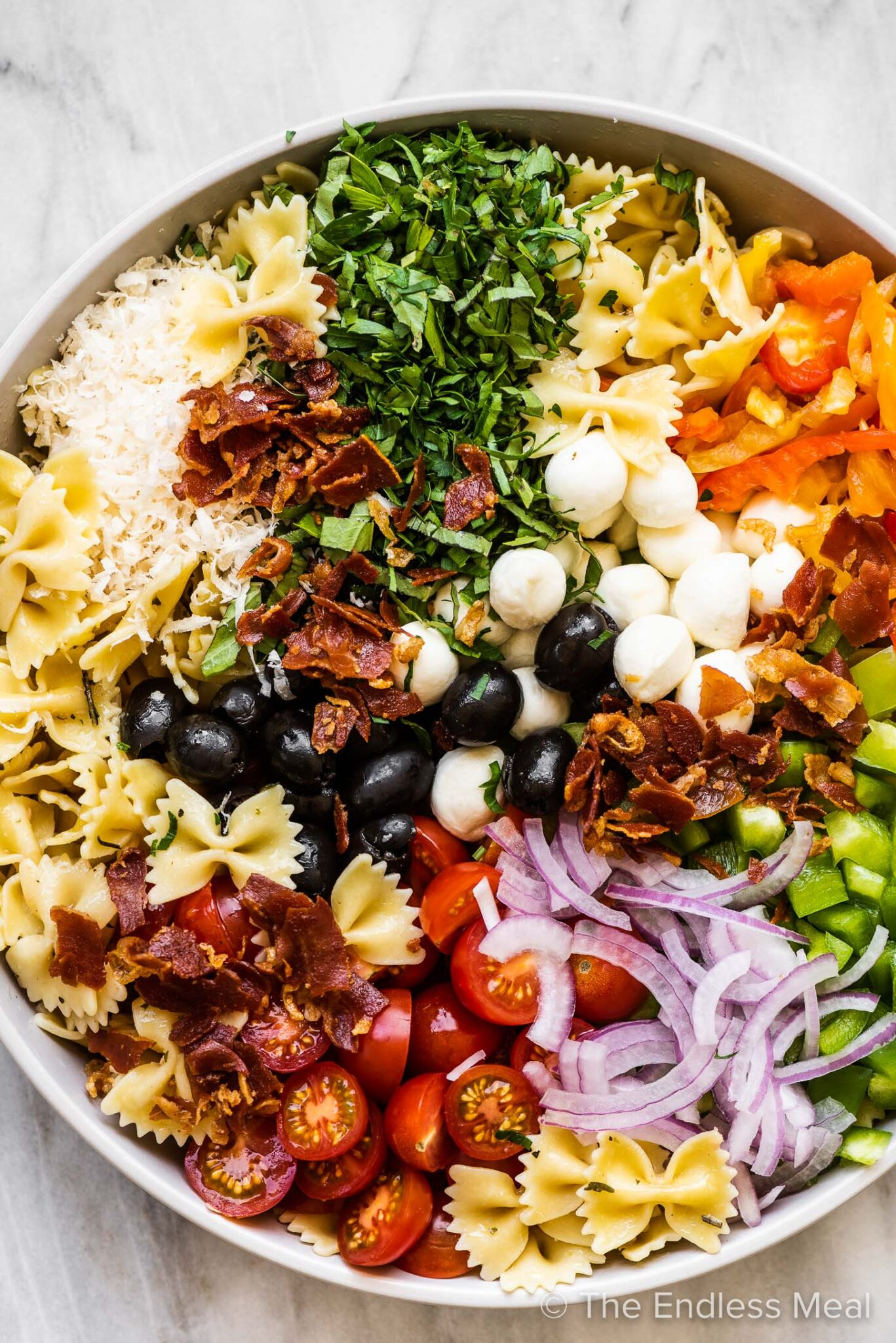 All the ingredients to make Italian pasta salad in a salad bowl.