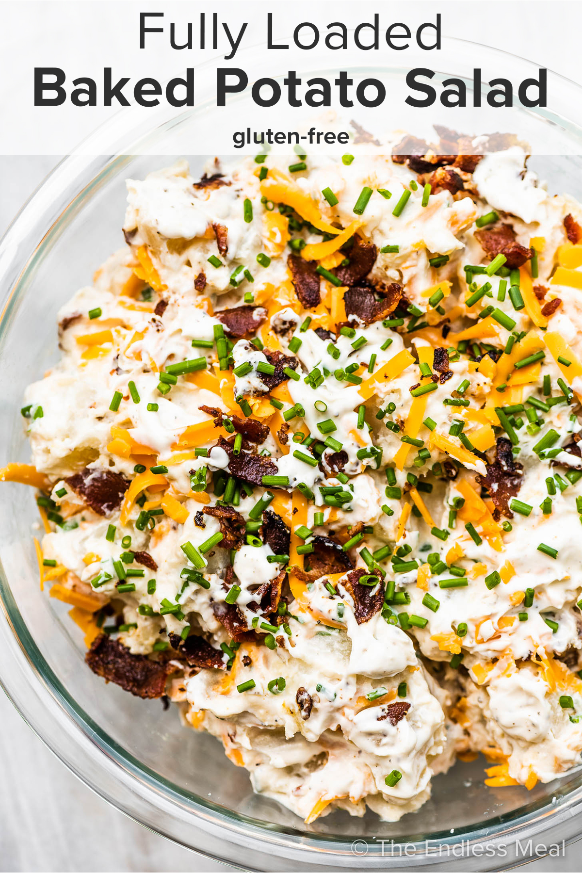 Loaded baked potato salad in a glass serving bowl with the recipe title on top of the picture.