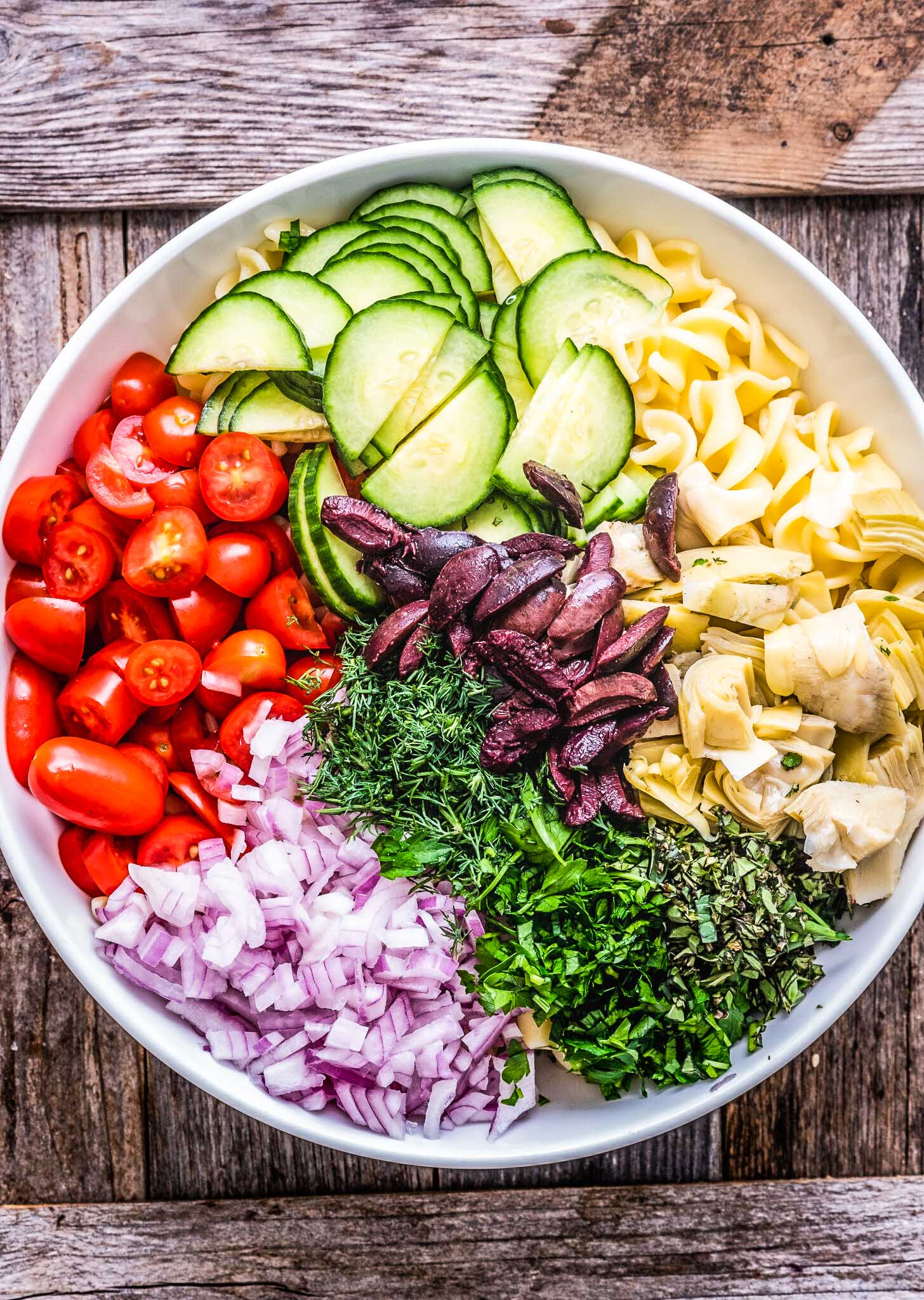 All the ingredients for Greek pasta salad in a mixing bowl.