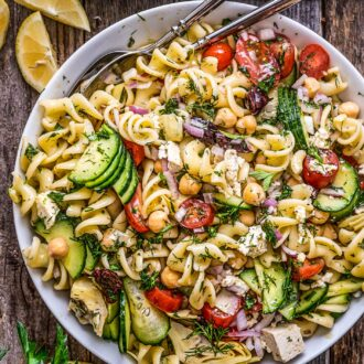 Greek pasta salad in a white bowl with tongs.