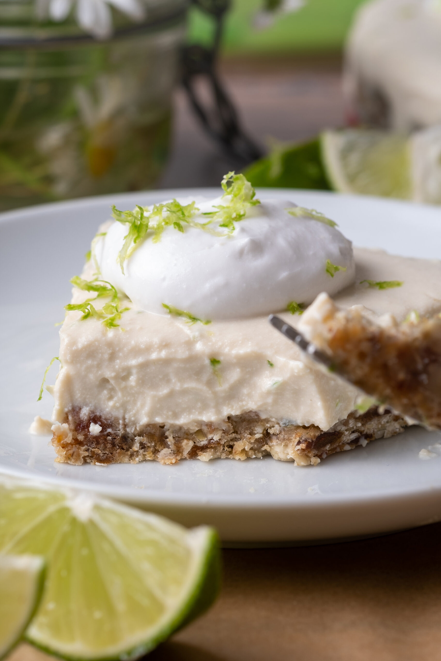 Healthy Key Lime Pie on a plate with a fork taking a bite.
