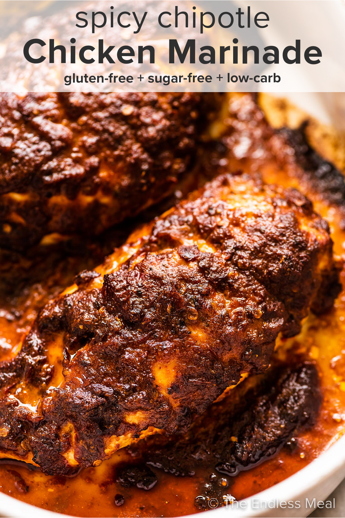 Spicy Chicken Marinade on chicken breasts in a baking dish and the recipe title on top of the picture.