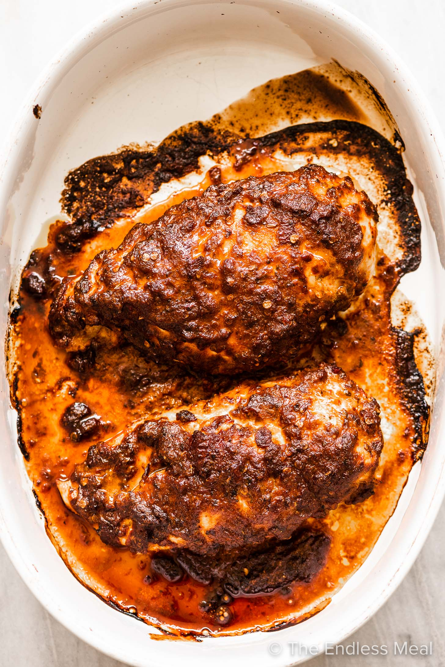 Chicken breasts marinated in a spicy chipotle marinade in a baking dish.