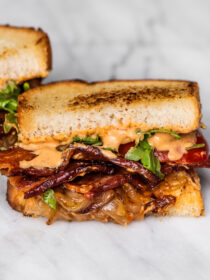 A bacon sandwich with lots of caramelized onions.