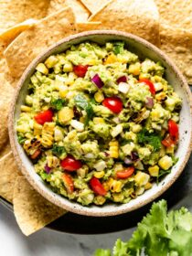 Corn guacamole served in a bowl with chips on the side