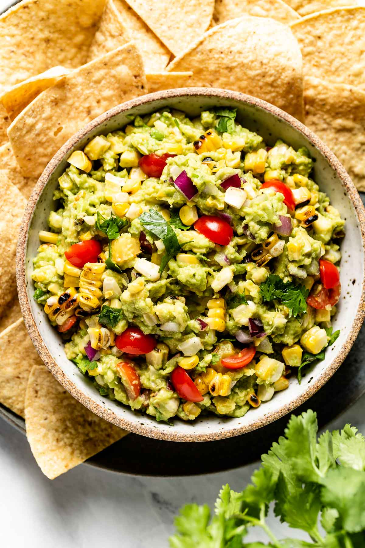 Corn guacamole in a bowl served with tortilla chips on the side