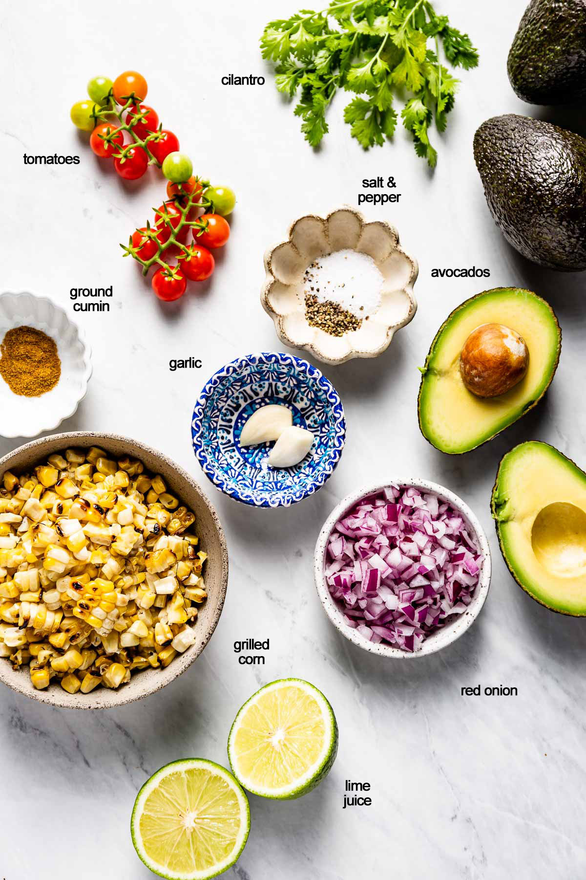 Ingredients for the grilled corn guacamole recipe portioned out on a marble backdrop