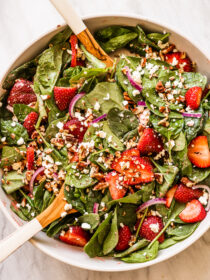 Strawberry Spinach Salad in a serving bowl with tongs.