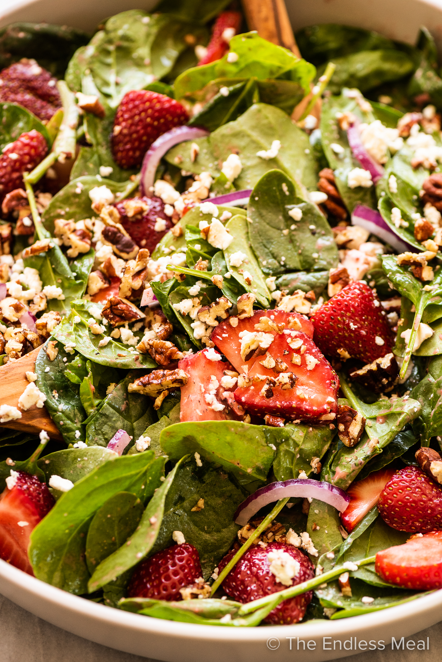 A close up of spinach and strawberry salad.
