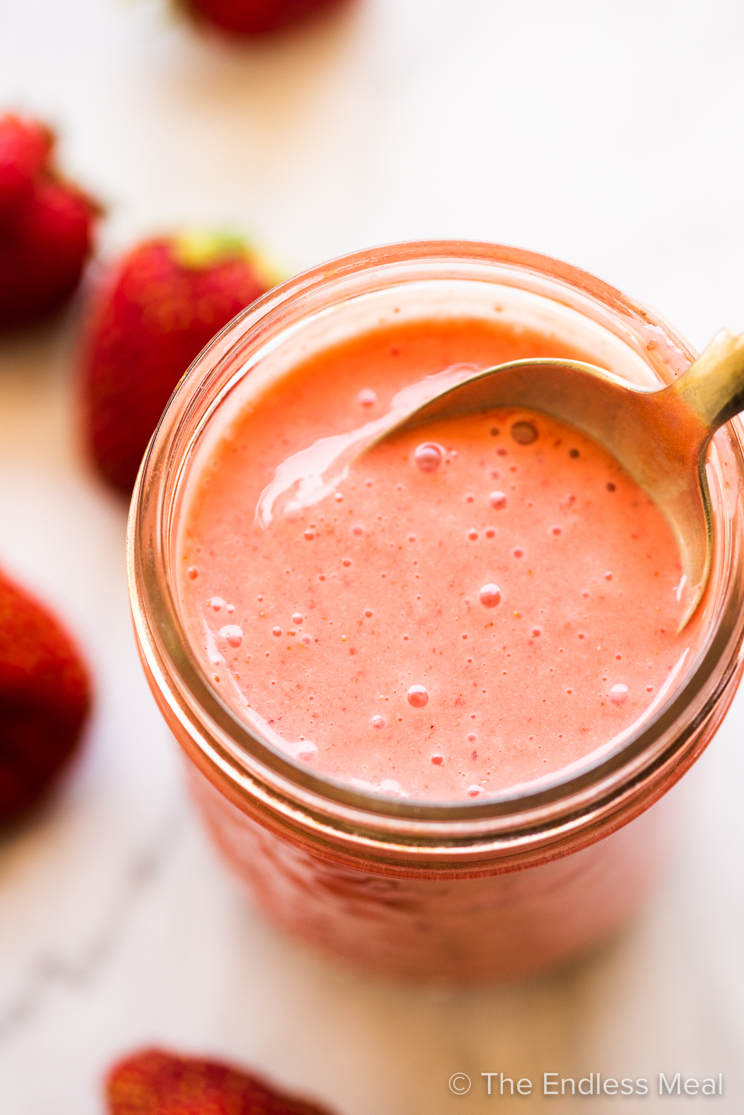 Strawberry vinaigrette in a glass jar with a spoon.