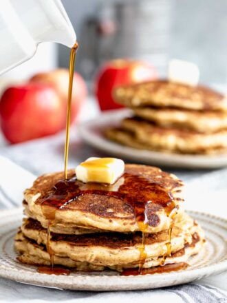 a stack of pancakes with maple syrup being poured over them