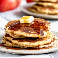 a stack of apple pancakes with butter and maple syrup on top