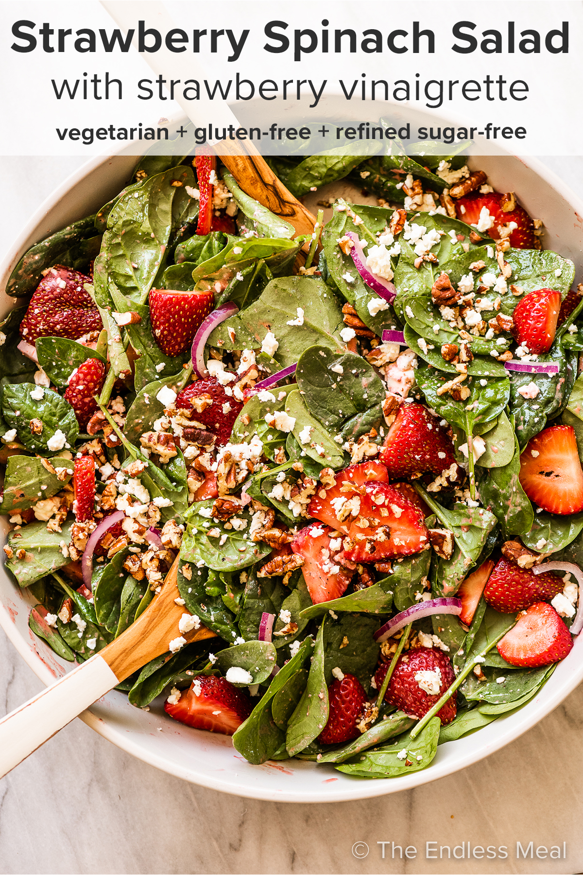 Strawberry Spinach Salad in a serving bowl with tongs and the recipe title on top of the picture.