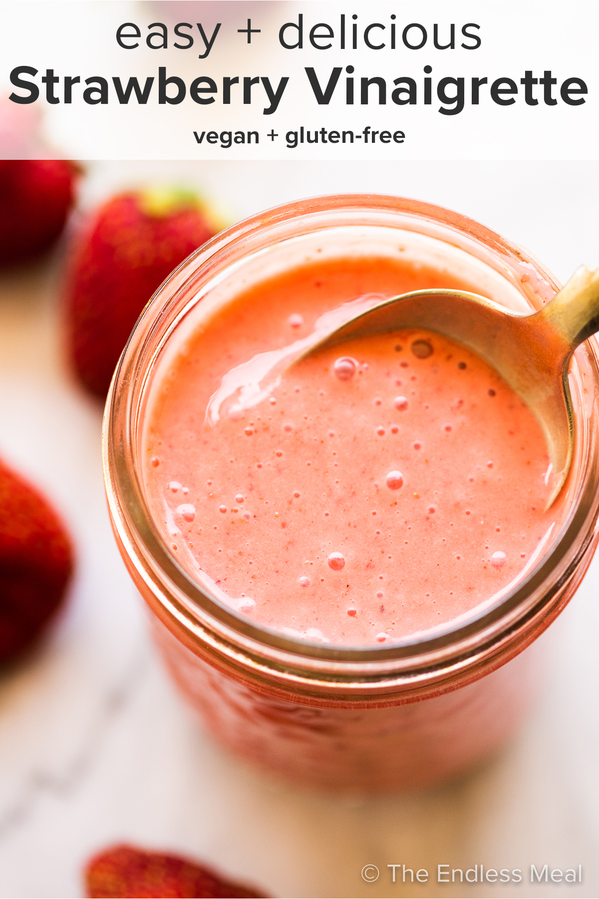 Strawberry vinaigrette in a glass jar with a spoon and the recipe title on top of the picture.