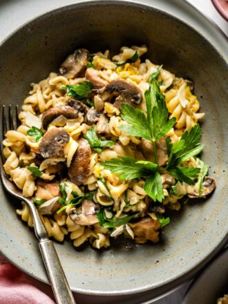 A bowl of chicken mushroom pasta topped off with parsley.