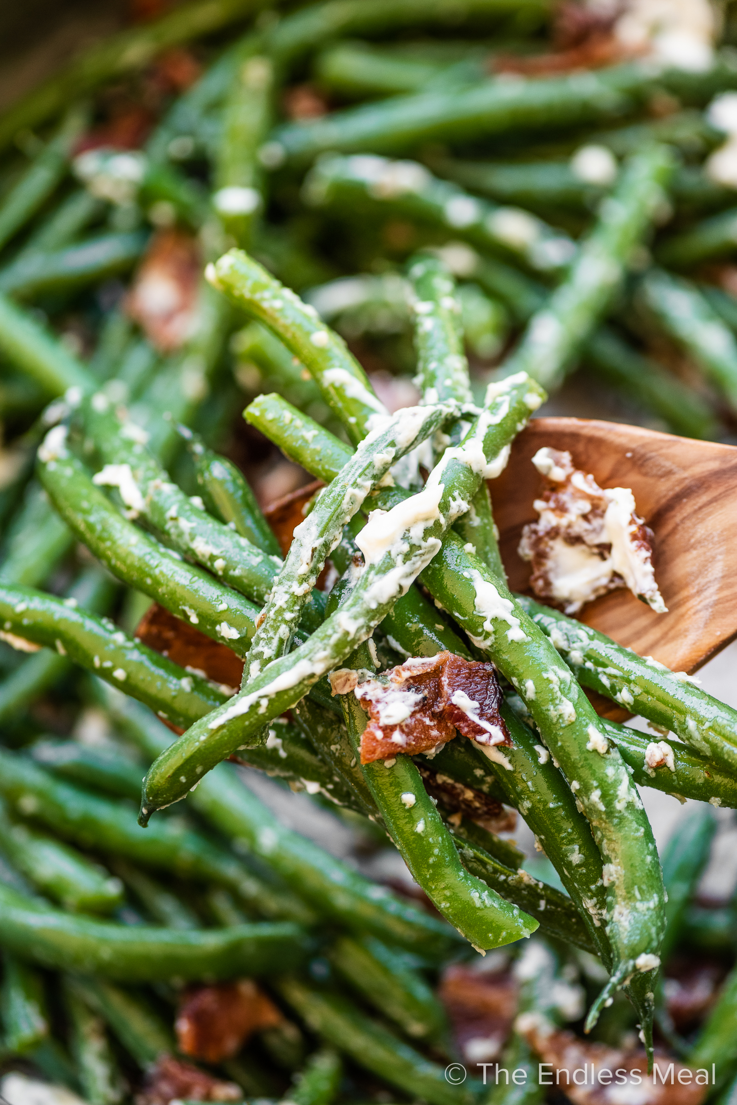 A close up of a spoonful of green beans with bacon.