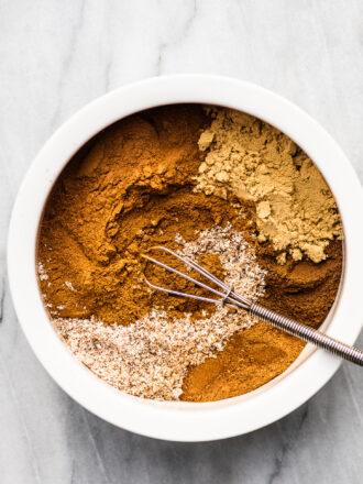 The spices to make Pumpkin Pie Spice in a white bowl with a whisk.