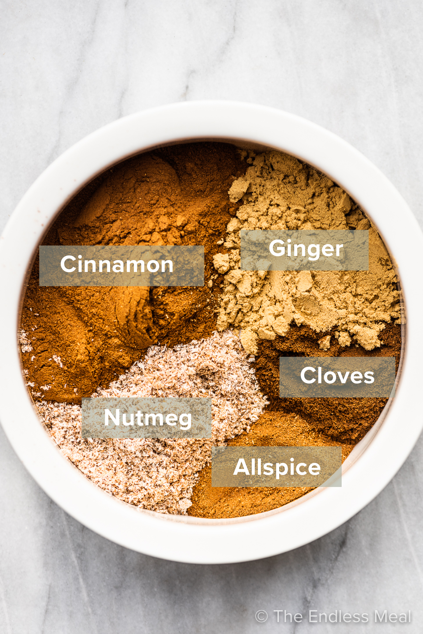 The ingredients to make this pumpkin pie spice recipe in a white bowl.