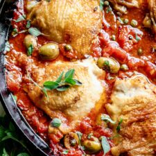 close up of crispy chicken thighs in tomato sauce with olives