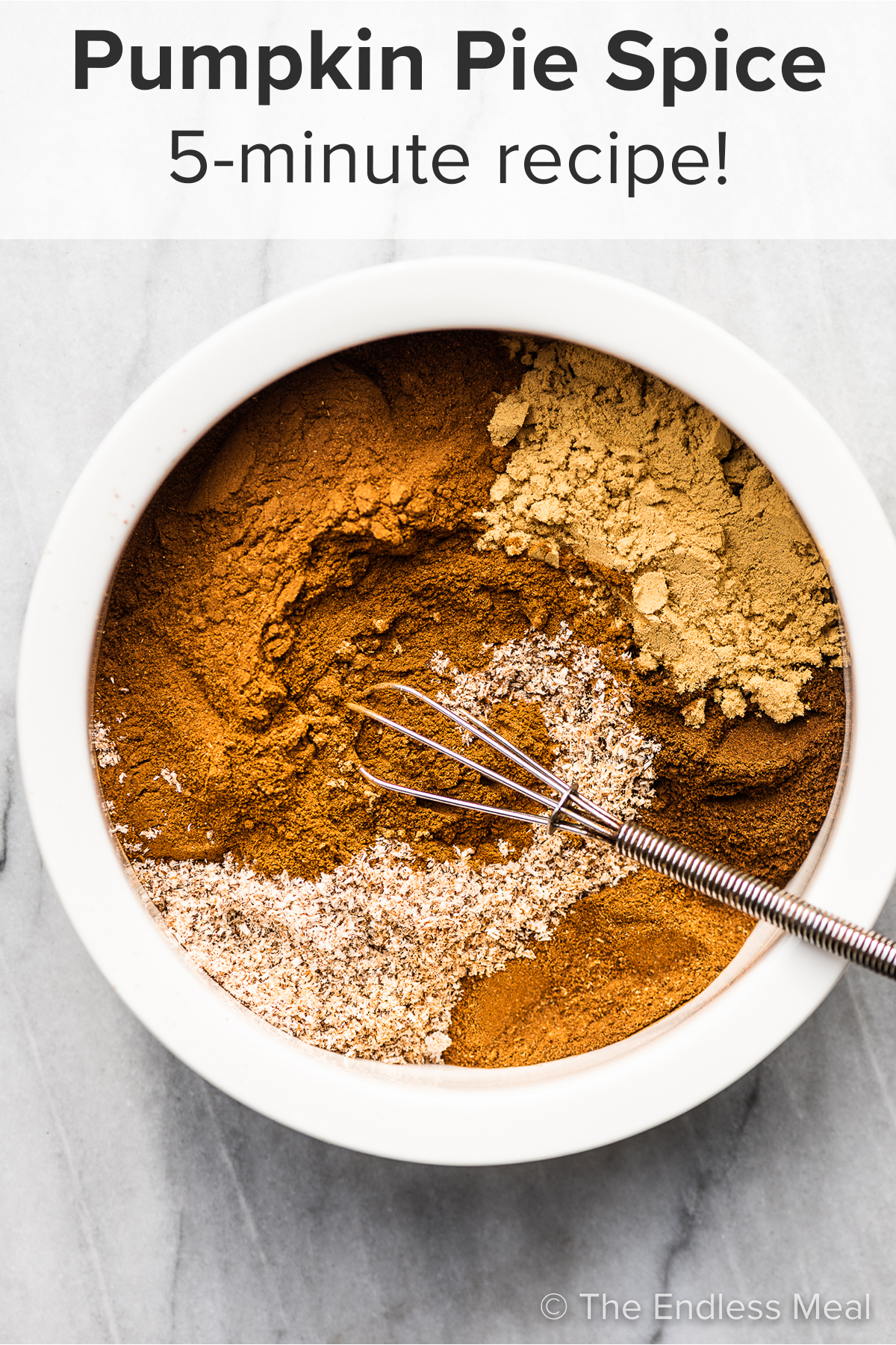 The spices to make Pumpkin Pie Spice in a white bowl with a whisk with the recipe title on top of the picture.