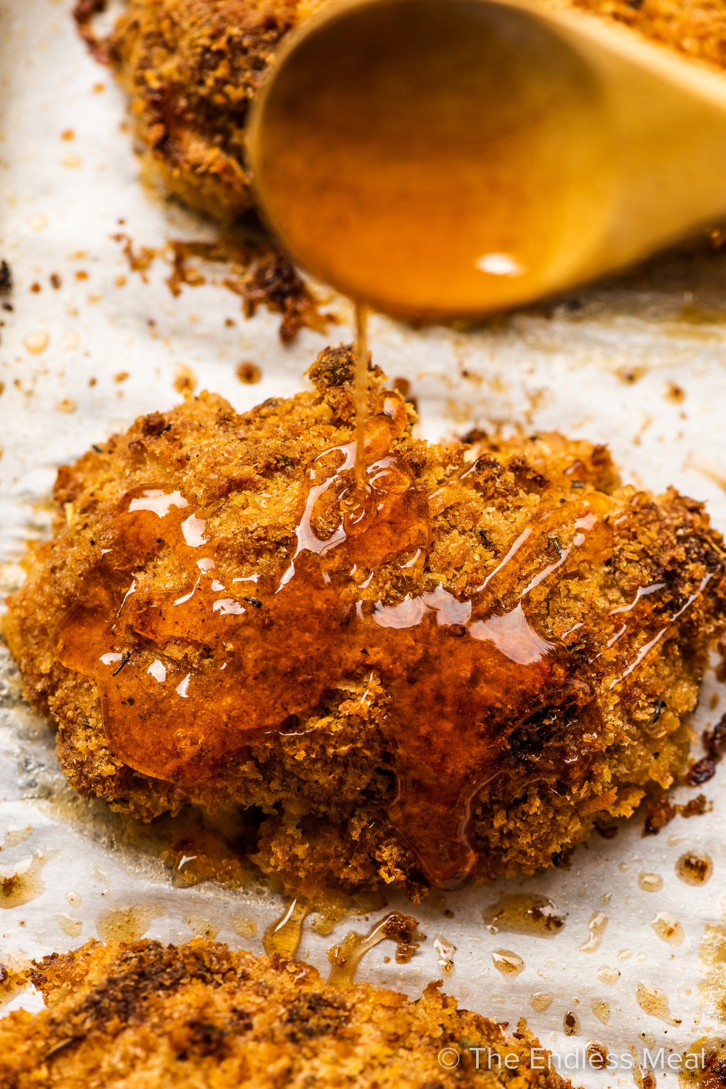 Hot honey being drizzled over crispy chicken.