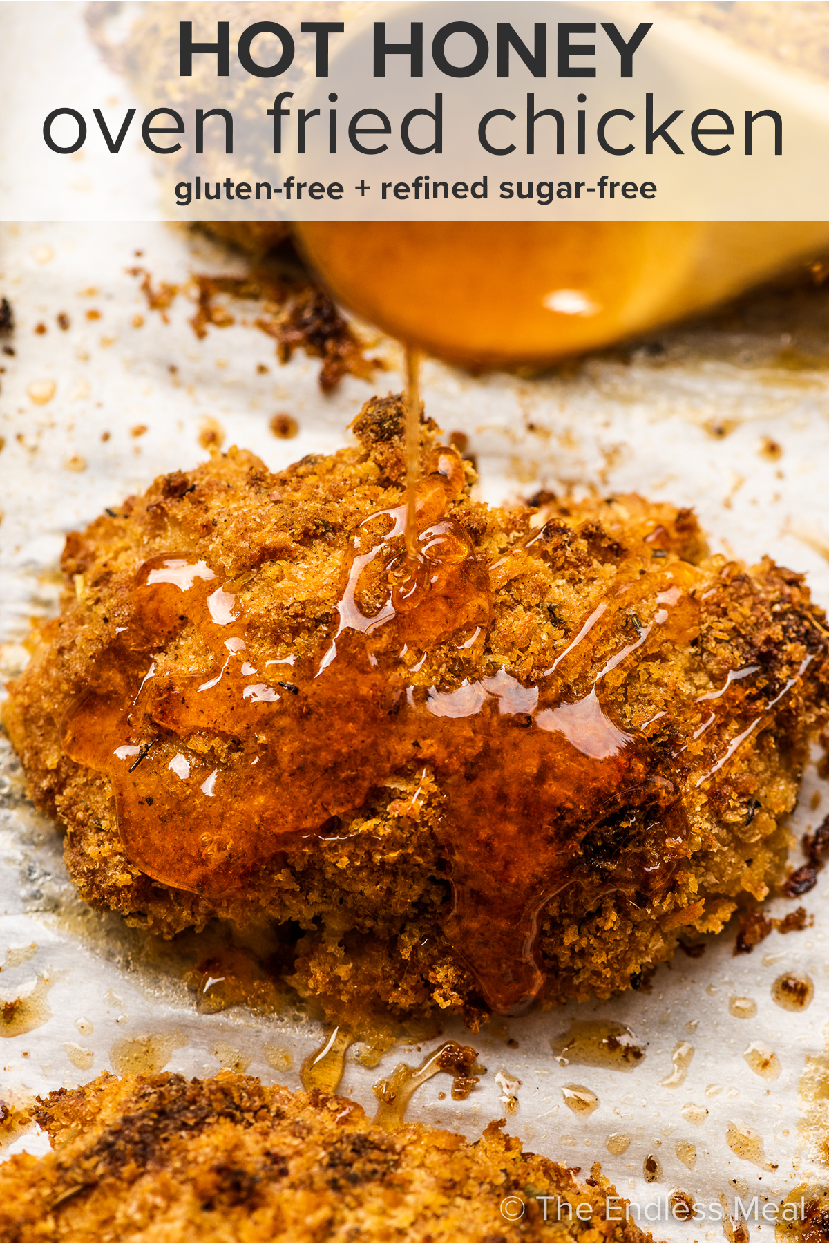 Hot honey being drizzled over crispy chicken and the recipe title on top of the picture.